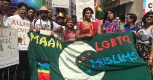 "Members of Imaan holding a banner with a crescent moon and the words ""Imaan LGBTQ Muslim"""