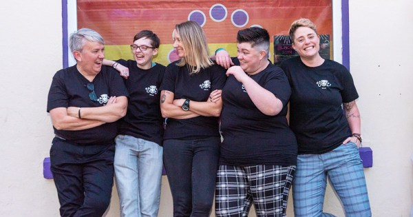 Five women in black tshirts pose happily outside a building