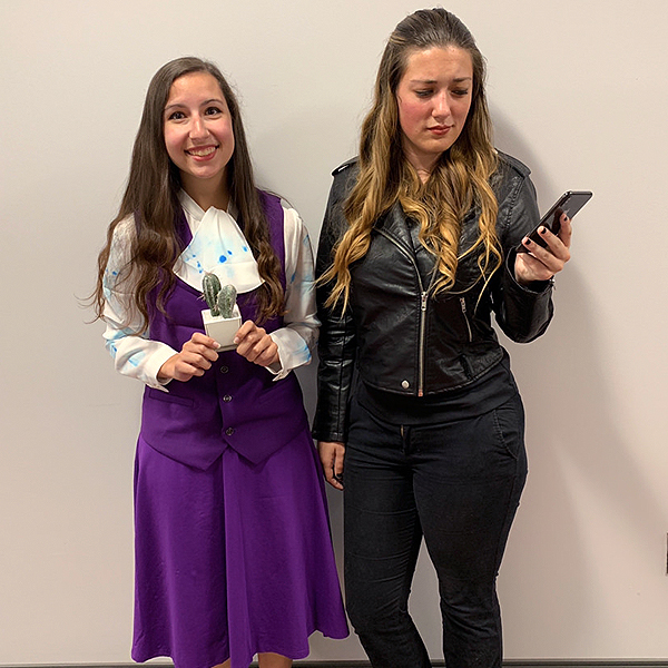 Two women dressed up in good Janet and Bad Janet Halloween costumes
