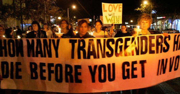 People holding a sign saying How many transgenders have to die before you get involved.