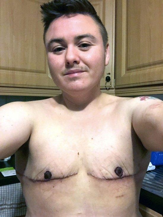 Young trans man taking a shirtless selfie