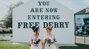 Wedding photo of Emma Bradley and Danielle Doherty in front of the Free Derry Corner