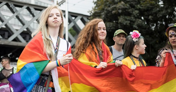 A group of young women holding a rainbow flag and marching in a Pride parade