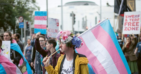 A Trans Pride march with a young man in the foreground with flowers on his head carrying a huge trans flag