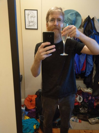 Jon Hanna taking a selfie in the mirror while holding a glass of shampain