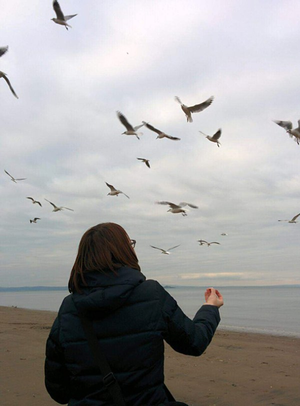 Russian woman at the beach looking at the sky and birds