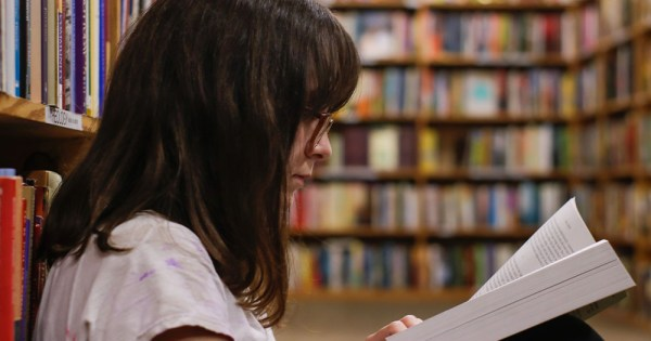 A young woman with glasses reading a book in a library