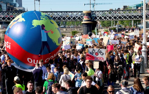 A crowd of marching young people holding signs and inflatable