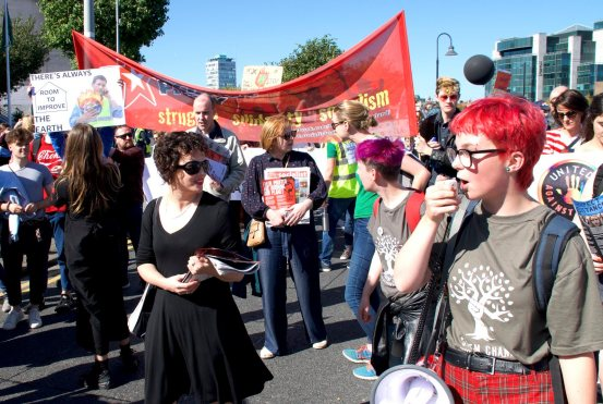 A crowd of marching young people holding signs and inflatables
