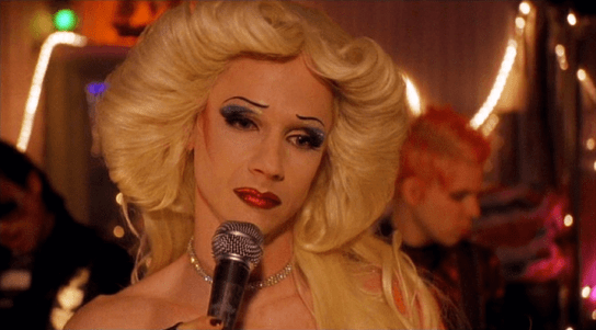 A drag artist with 1970's style hair holds a microphone and looks wistfully into the distance