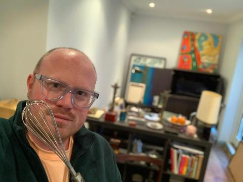 A bald man with glasses holds a whisk