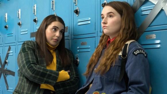 Two teenage girls lean against a row of lockers