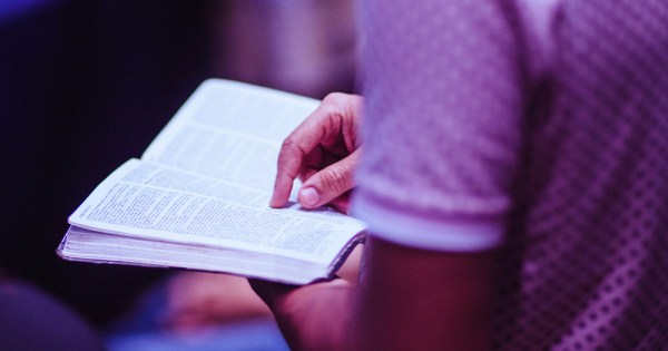 A close up image of a young man's torso as he sits pointing at an open bible on his lap