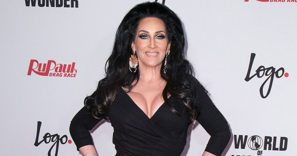 A glamorous woman in a black dress, her dark hair coiffed hugely