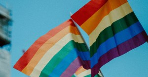 Two rainbow flags touching in the sky