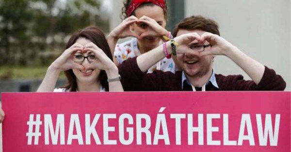 Three young people holding a sign and making a heart shape with their hands