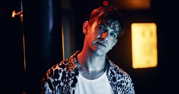 A young man in a vest and shirt poses moodily while lit by neon light