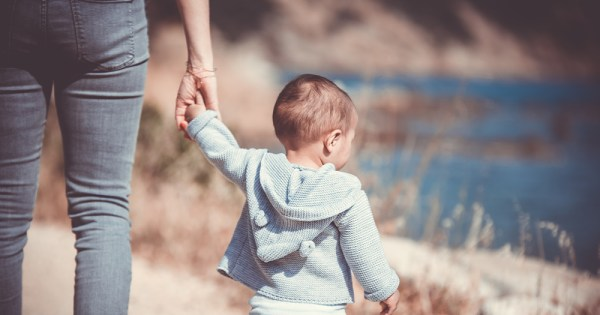 The torso of a woman holding a toddler's hand as they walk along a hill overlooking the sea