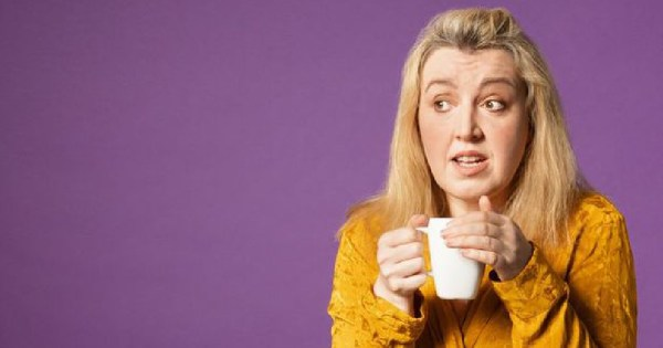 A blonde surprised looking woman holds a mug