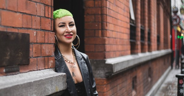 A young woman with green hair and tattoos smiles at the camera on a city street
