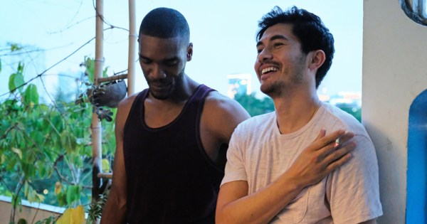 Actors Henry Golding and Parker Sawyers laughing during a scene from 2019 film Monsoon