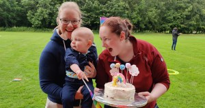 Two women hold a baby and a birthday cake while standing in a park
