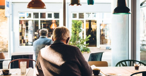 Two older men sit in a coffee shop, their backs to the camera