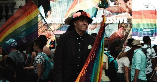 an LGBT+ person holds a felt rainbow flag in Paseo de la Reforma, Mexico City, México