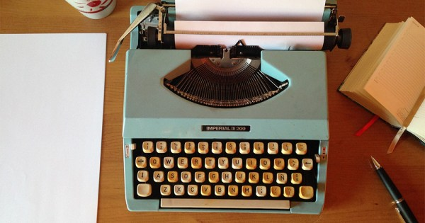 A typewriter, a pen and a book on a desk