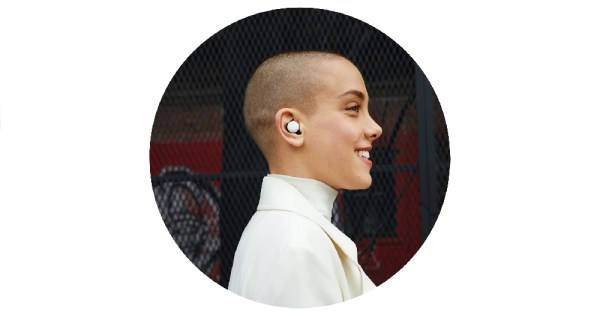 image of a person with a shaved head wearing the google pixel earbuds