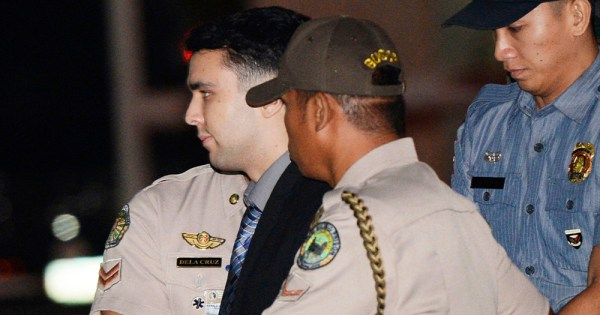 A man is escorted by police officers