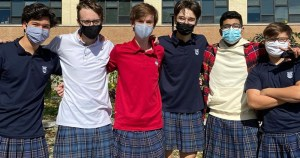 a group of male students wearing skirts pose for a photo