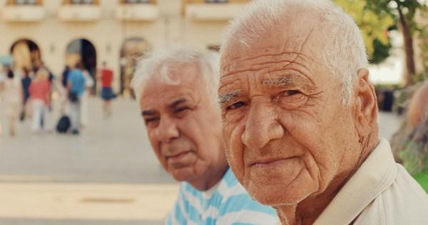 Two old men sit side by side