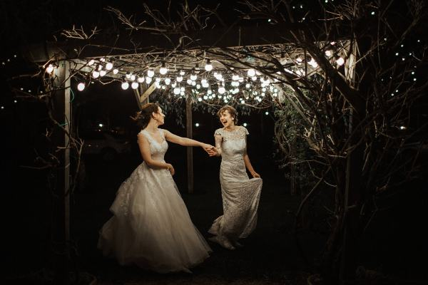 Sophie and Claire in their wedding dresses twirling around during their wedding at the Millhouse