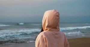 A woman with her hood pulled up stares at the sea