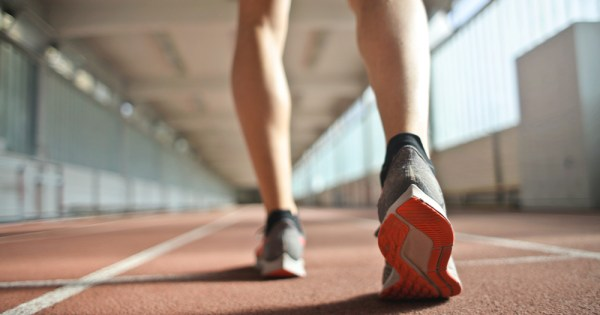 A close up of legs about to run on a track