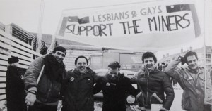 Five smiling men hold a banner above their heads