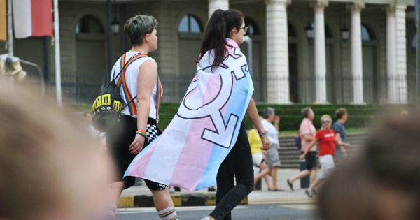 young people walking together, one wrapped in a trans flag