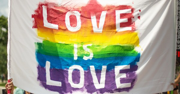 A banner reading Love Is Love in rainbow paint