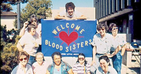 A group of smiling women holding a sign saying Blood Sisters