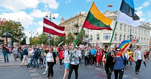 Smiling people on a city street waving huge flags