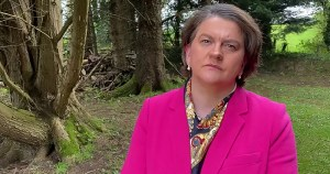 An annoyed looking woman in a suit stands in a forest
