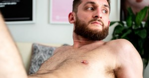 Naked bearded man laying in bed from Dublin photoshoot for Elska magazine