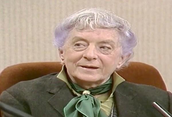 An elderly man wearing a green tie sits on a TV set