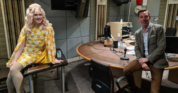 A drag queen and an interviewer sitting in a radio studio
