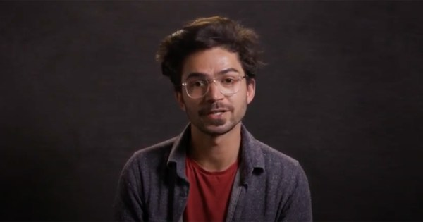 A bearded young man with glasses speaks to the camera