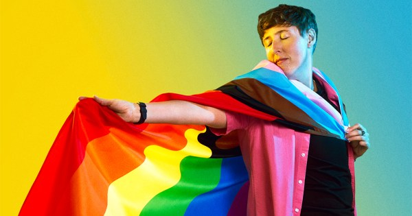 coming out trans: portrait of trans man Adam draped in a rainbow flag