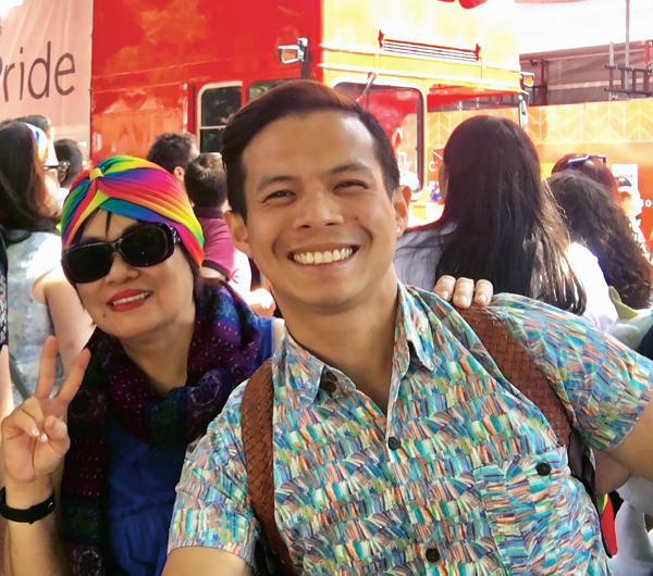 Roberto Sy talks about coming out in the workplace - In the photo, a smiling man, behind him a woman wearing a rainbow headband and sunglasses.