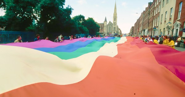 A rainbow LGBTQ+ Pride flag billows over a street. In the background you can see a church and several other buildings.