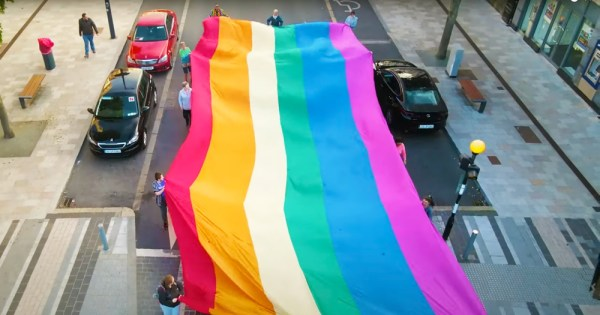 a still from 'now you see us' shows a large Pride flag being carried by a group of people down a street